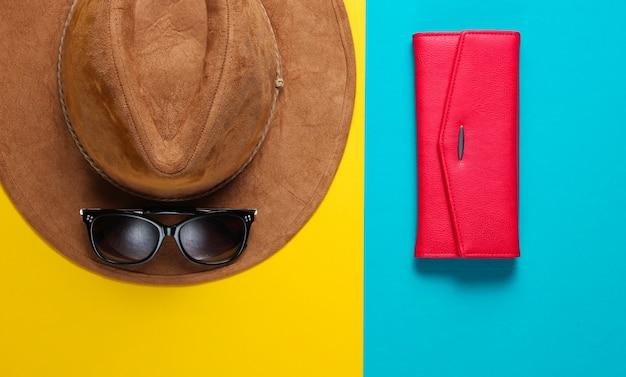 サングラスと帽子を感じた、色付きのテーブルに財布。おしゃれな季節のアクセサリー
