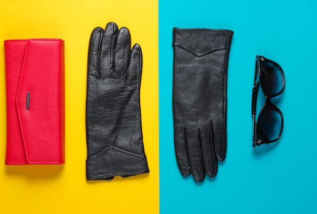 赤い革の財布、サングラス、手袋の色付きのテーブルのクローズアップ。上面図
