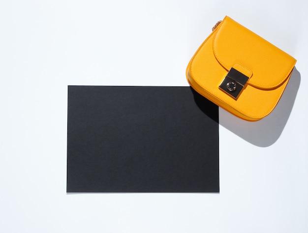 コピースペース、灰色のテーブルの上に黄色の袋の黒い紙。クリエイティブファッションテーブル