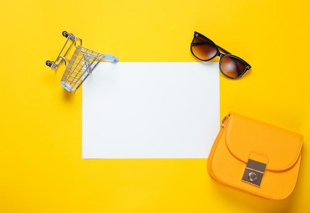 コピースペース、ミニショッピングトロリー、バッグ、サングラス、黄色のテーブルの紙の白いシート。クリエイティブなショッピングテーブル