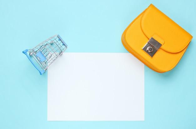 コピースペース、ミニショッピングトロリー、青いテーブルの上にバッグの紙の白いシート。クリエイティブなショッピングテーブル