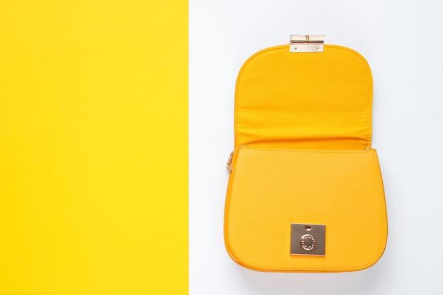 色付きのテーブルに革のバッグを開きます。トップビュー、ミニマリズム