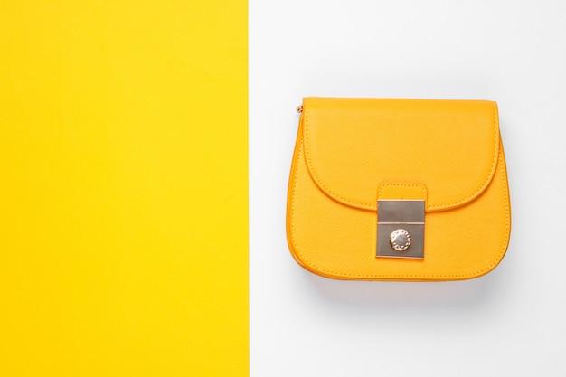 色付きのテーブルに黄色の革のバッグ。トップビュー、ミニマリズム
