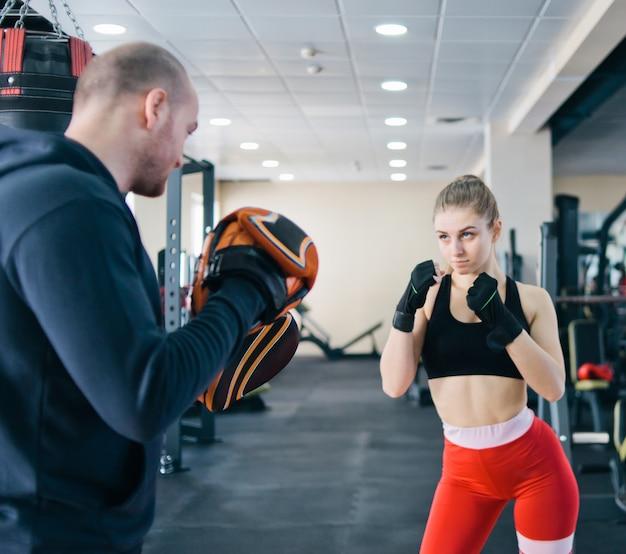 金髪の女性トレーニングパンチ、ジムで男性トレーナーに合わせて
