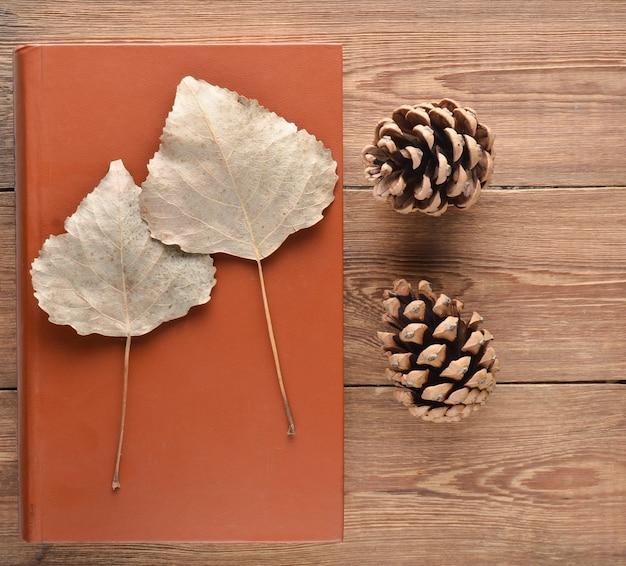 Высушенные листья на книге, сосновые шишки на деревянном столе. вид сверху. домашний гербарий.