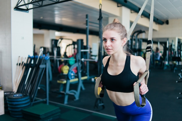 Молодая блондинка в спортивной одежде, делая упражнения с фитнес-ремнями в тренажерном зале