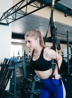 Женщина детенышей подходящая делая тренировку с планками фитнеса в спортзале