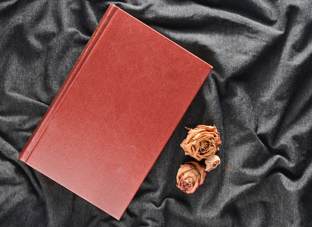 Книга и высушенные розы на серой предпосылке ткани. вид сверху.