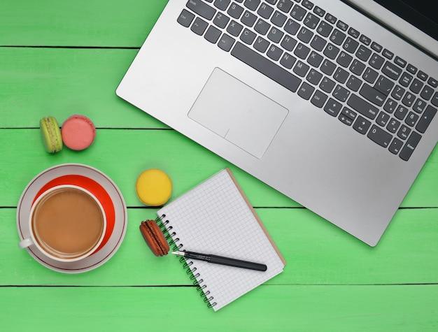 Вид сверху ноутбук, миндальное печенье и чашка кофе с ноутбуком