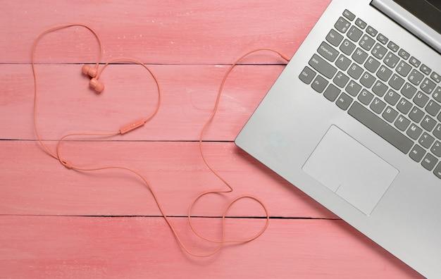 Вид сверху ноутбука и наушников в форме сердца
