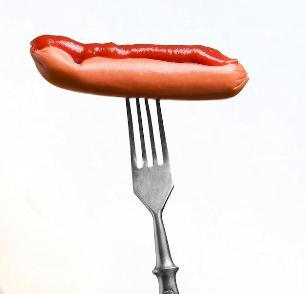 Крупным планом на металлической вилке, держа хот-дог