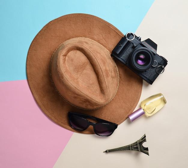 旅行、放浪癖の概念への情熱。フランス、パリへの旅行。パステル紙の背景に帽子、フィルムカメラ、サングラス、香水瓶、エッフェルタワーレイアウトのお土産像を感じた。平干し。