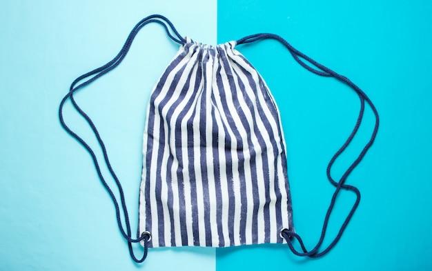 Полосатая ткань пляжный рюкзак на синем столе.