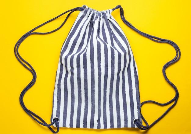 Полосатая ткань пляжный рюкзак на желтом столе.
