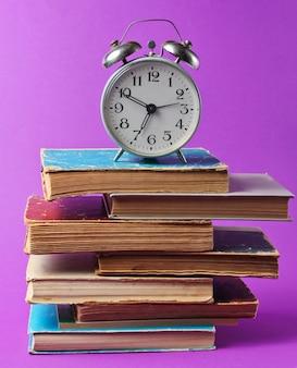 Ретро будильник на стопку старых книг на фиолетовый таблицы.