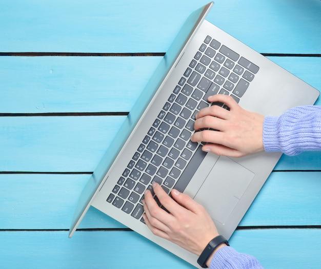 青い木製のテーブルにノートパソコンのキーボードで手を入力しています。フリーランスの概念は、インターネットで動作します。上面図。コピースペース。