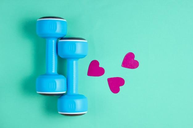 Пластмассовые гантели, декоративные сердечки на пастельном мятном столе. здоровый образ жизни, забота о сердце