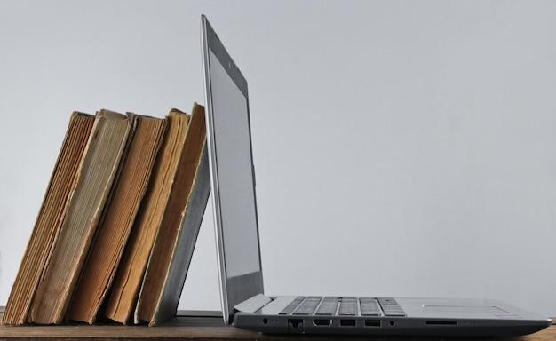 現代のラップトップと白い壁に木製の棚の上の古い本をスタック