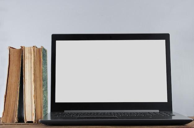 現代のラップトップと白い壁の表面に木製の棚の上の古い本をスタックします。