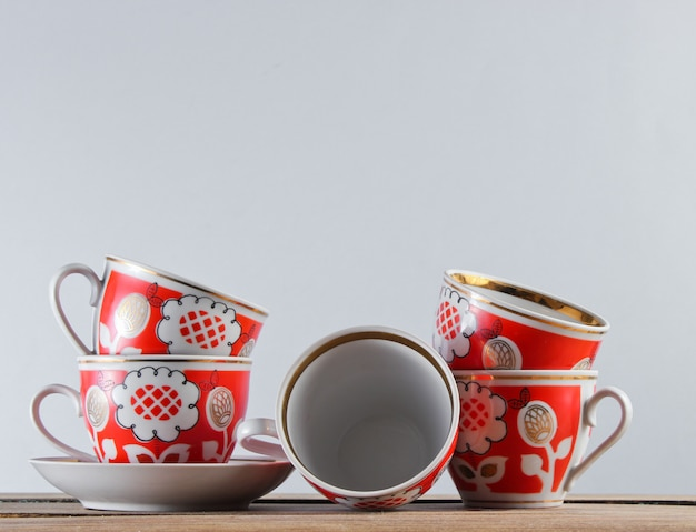 Много старинных керамических чашек на деревянном столе против белой стены