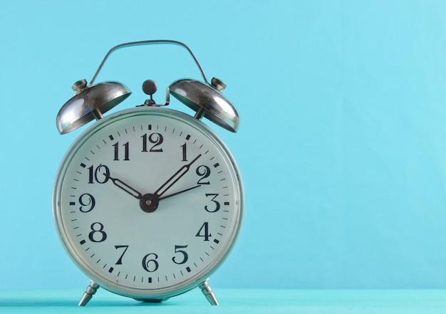 青い表面にレトロな目覚まし時計のクローズアップ。