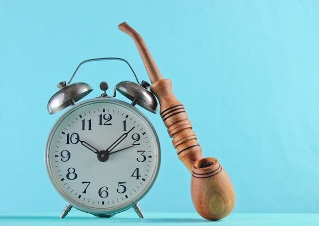 青い表面にレトロな目覚まし時計と禁煙パイプのクローズアップ。