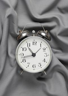 灰色のシルクのベッドカバーにレトロな目覚まし時計。