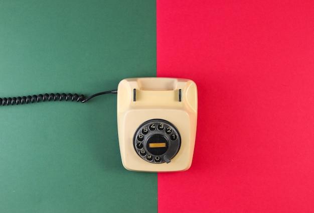 Ретро роторный телефон на поверхности красно-зеленой бумаги.