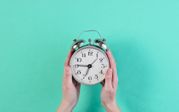 女性の手が青い表面にレトロな目覚まし時計を保持します。