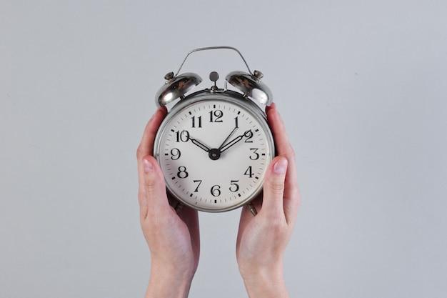 女性の手は灰色の表面にレトロな目覚まし時計を保持します。
