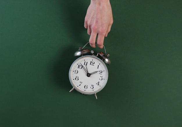 女性の手が緑の表面にレトロな目覚まし時計を保持します。