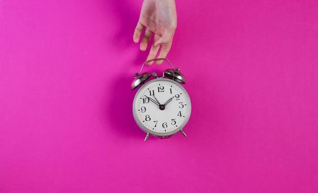 女性の手がピンクの表面にレトロな目覚まし時計を保持します。