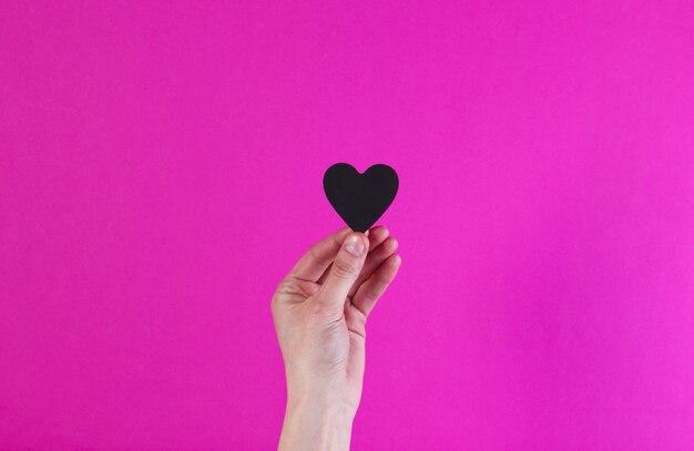 女性の手はピンクの表面に黒の装飾的な心を保持します。