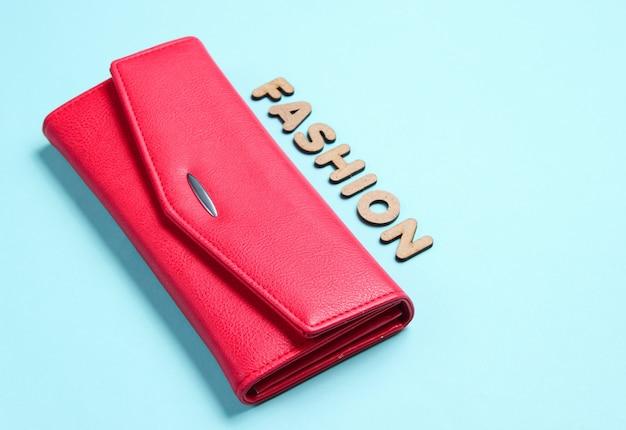 Красный кошелек на синей поверхности с текстом моды с буквами.