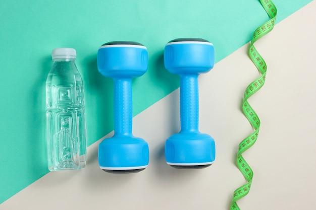 ダンベル、定規、着色された表面上の水のボトル。