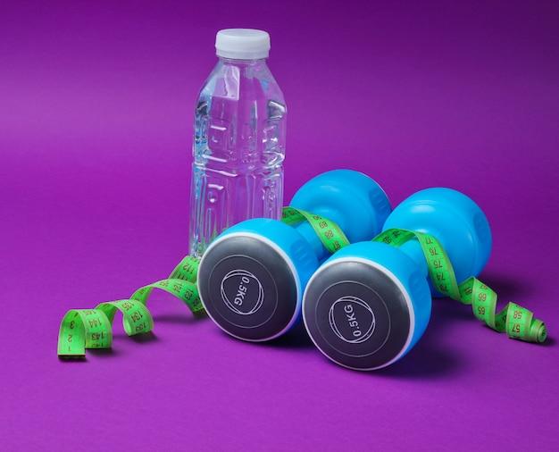ダンベル、定規、紫色の表面に水のボトル。