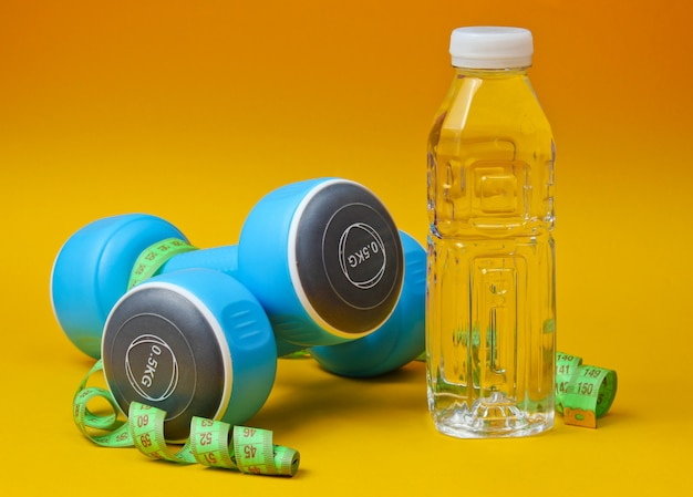 ダンベル、定規、黄色の表面に水のボトル。