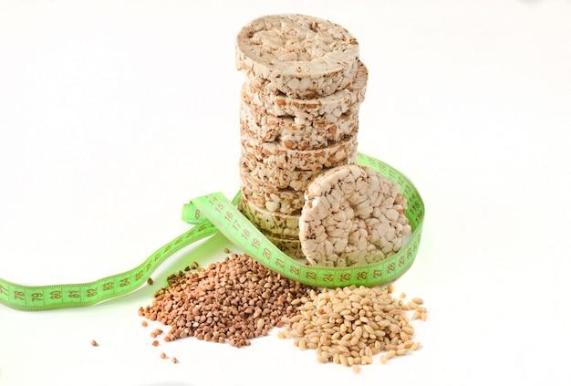 Кудрявый круглый диетический хлеб пригодности риса гречихи обернутый при правитель изолированный на белой предпосылке. еда для уменьшения.