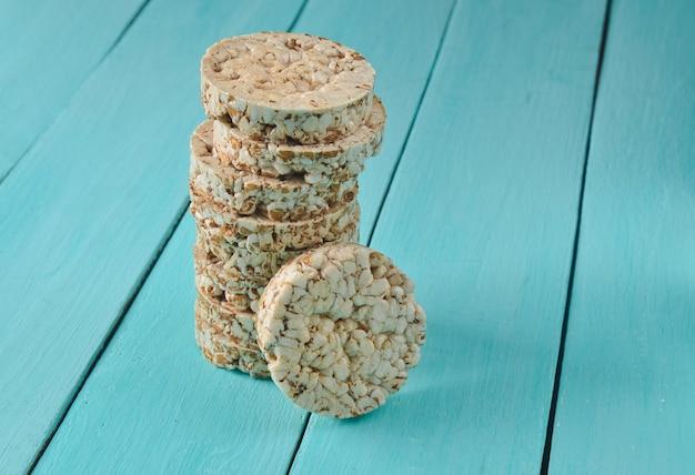青い木製のテーブルに定規で包まれたサクサクした丸い食事そば米フィットネスパン。減量のための食物。