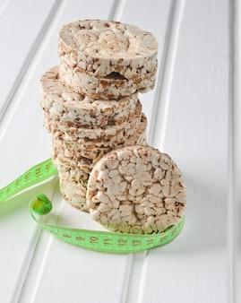 白い木製のテーブルに定規で包まれたシャキッとした丸い食事そば米フィットネスパン。減量のための食物。