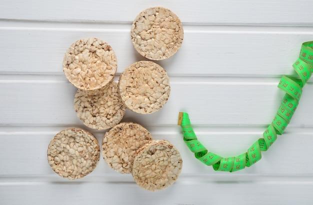 カリカリの丸い食事そば米フィットネスパンと白い木製のテーブルの定規の平面図です。減量のための食物。