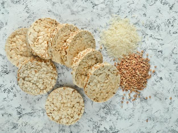 Взгляд сверху кудрявого круглого диетического хлебца фитнеса риса гречихи на конкретной таблице. пища для похудения.