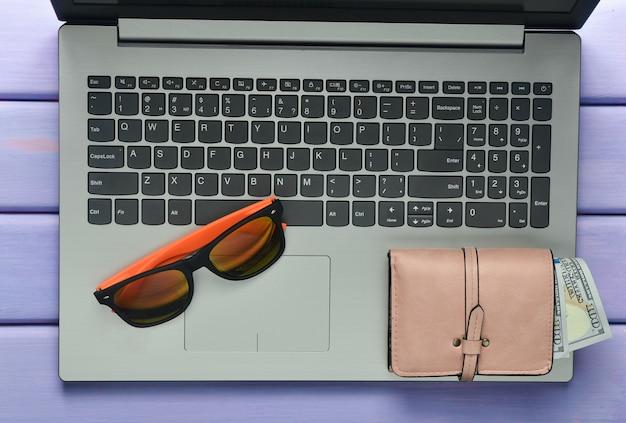 フリーランスのビーチリゾートでのウェブワークのコンセプト。ラップトップ、サングラス、紫の色の木製テーブルの上の財布。上面図。