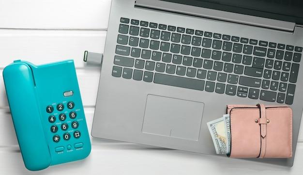 Интернет работа, фриланс концепция. офисный телефон, ноутбук, флэш-накопитель, кошелек на белый деревянный стол. вид сверху.