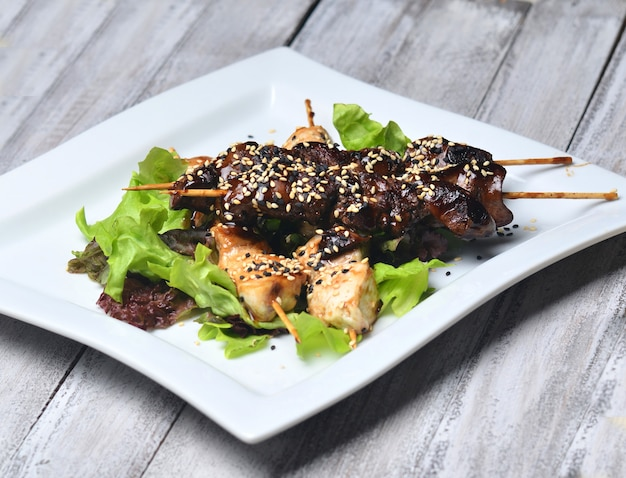 皿にゴマと焼き鳥。木製テーブルの上の棒で揚げた鶏肉と鶏レバー。