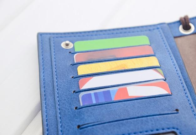白い木製のテーブルにクレジットカード付きの財布。