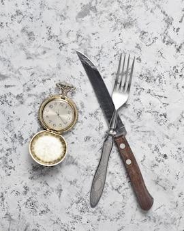 ポケット付きヴィンテージ時計、フォーク、ナイフ、灰色のコンクリートテーブル。朝食の時間。上面図。