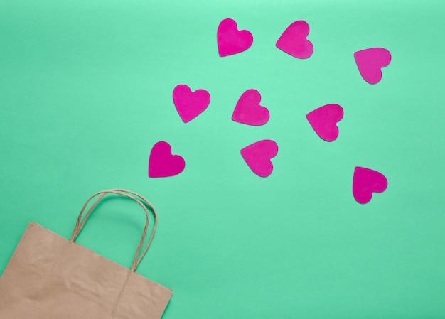 ショッピングの愛の概念。ショッピングと色付きのミントの背景にたくさんの装飾的な心のための紙袋。バレンタイン・デー。上面図。