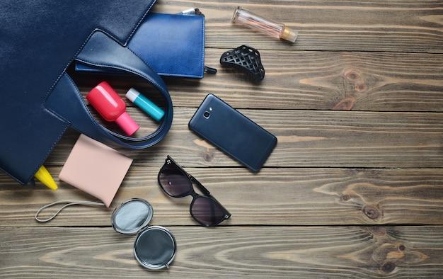 婦人用バッグの中身は?女性の流行のアクセサリー。スマートフォン、香水瓶、パワーバンク、ミラー、サングラス、口紅。上面図。