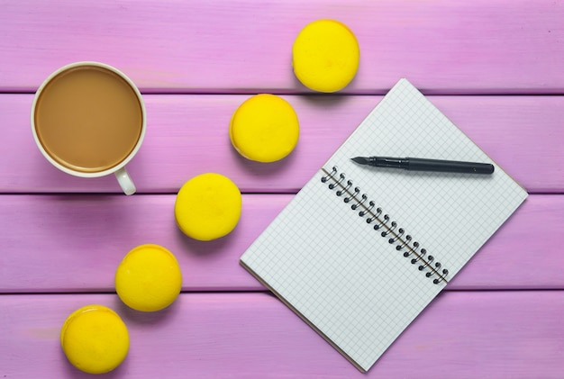 ペン、一杯のコーヒーと紫の木製のテーブルに黄色のマカロンのノート。ミニマリズムのトレンド。上面図。フラット横たわっていた。